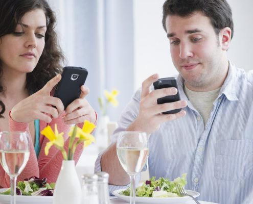 couple texting at dinner